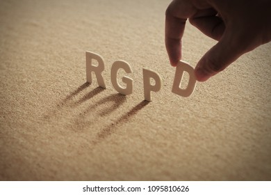 RGPD wood word on compressed or corkboard with human's finger at D letter.