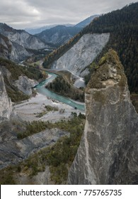 Rheinschlucht Graubünden Valley with blue river meandering through rugged gorge with tree on massive rock in foreground aerial view