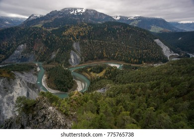 Rheinschlucht Graubünden Valley with deep blue river meandering through rugged gorge with coniferous forest and snow capped mountains on an overcast day viewpoint
