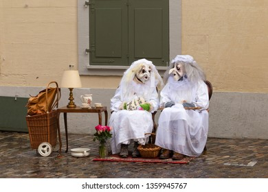 Rheinsprung, Basel, Switzerland - March 13th, 2019. Two carnival participants disguised as old ladies in white dressing gowns