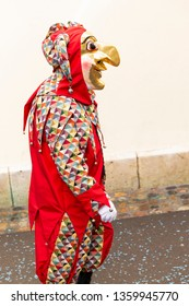 Rheinsprung, Basel, Switzerland - March 13th, 2019. Portrait of a carnival participant in red costume with gold colored mask