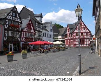 RHENS, GERMANY - JULY 04, 2017: View of street with beautiful half timbered houses and people relaxing at outdoor restaurant in little town Rhens in Germany