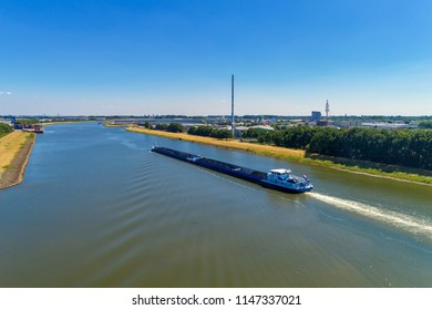 Rhine - Netherlands, July 14, 2018: aerial view commercial ship crossing the River Rhine in an area of the Netherlands