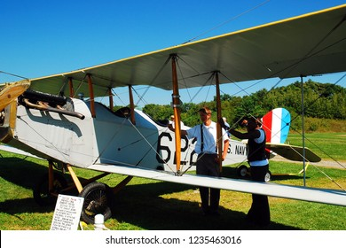 Rhinebeck, NY, USA September 4, 2009 Two men, dressed in period, early 20th Century clothing, examine a vintage Curtiss JN 4H2 at a museum in Rhinebeck New York