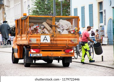 RHINELAND-PALATINATE, GERMANY - AUGUST 27 : German people sweeper working clean and keep garbage and push garbage truck on the road at Speyer town on August 27, 2017 in Rhineland Palatinate, Germany