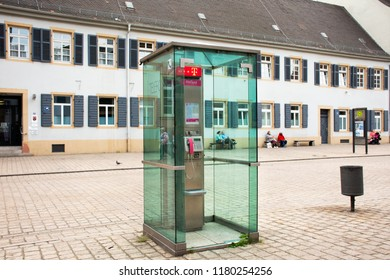 RHINELAND-PALATINATE, GERMANY - AUGUST 27 : Public telephone on pathway beside traffic road in small alley for people use phone at Speyer town on August 27, 2017 in Rhineland Palatinate, Germany