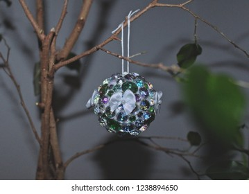 Rhinestone ornament hanging from ficus tree.