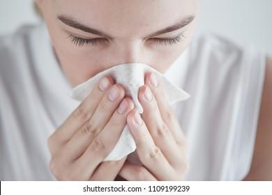 Rhinitis. Girl with napkin on white background