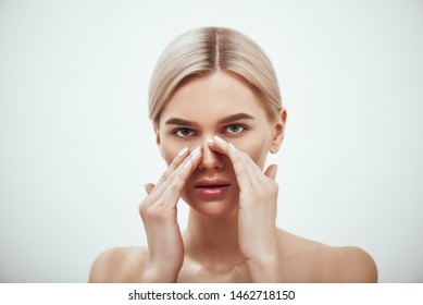 Rhinoplasty - nose surgery. Portrait of attractive blonde woman touching her nose and looking at camera while standing against grey background