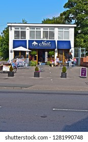 Rhiwbina, Cardiff County Borough / Wales UK - 8/29/2018: 'Nest' A popular upmarket independent retailer of Gifts and Homeware in the Cardiff suburb of Rhiwbina. Family group sitting outside at table.