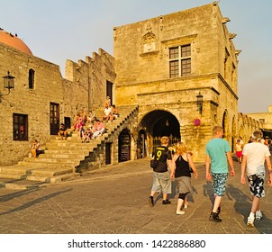 Rhodes, Greece - 07/22/2008: Tourists on the historic Hippocrates Square, in the Old Town center of the island of Rhodes, Greece. People sitting on steps, sunset time.