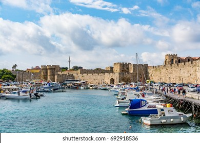 Rhodes, Greece - 17 April, 2017: Panoramic view of the fishing harbor and old town walls in Rhodes