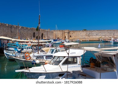 RHODES, GREECE - AUGUS 2020: Moored shipping boats near the walls of old city fortress.