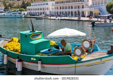 RHODES, GREECE - AUGUST 2020: Fisherman in a boat is repairing fishing equipment.