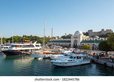 RHODES, GREECE - AUGUST 2020: Moored yachts and old terminal building of Rhodes port.