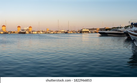 RHODES, GREECE - AUGUST 2020: Sunset above old windmills at main seaport of the old town