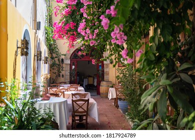 RHODES, GREECE - AUGUST 2020: Traditional Greek yard with tables and bougainvillea flowers, empty and without people at Rhodes island,Greece