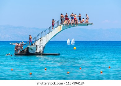 RHODES, GREECE - JULY 4, 2015: Many people having fun on diving board at Elli Beach, the main beach of Rhodes Town