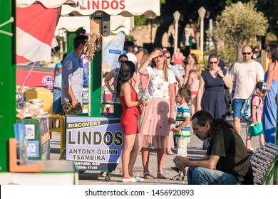 Rhodes, Greece - June 02, 2018. female tourist talking with female small cruise boat operator on the busy with people promenade in Mandraki Harbour