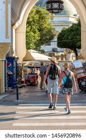 Rhodes, Greece - June 02, 2018. Daytime view of the entry to Mandraki and male couple crossing a road