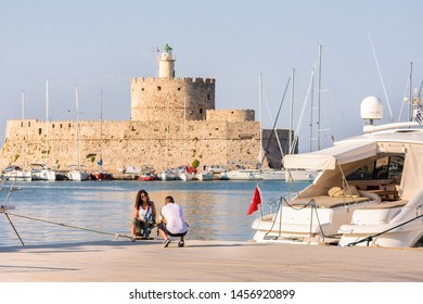Rhodes, Greece - June 02, 2018. St.Nicolas fortrees seen from promenade rhodes and couple taking photographs next to the luxury boat on sunny day