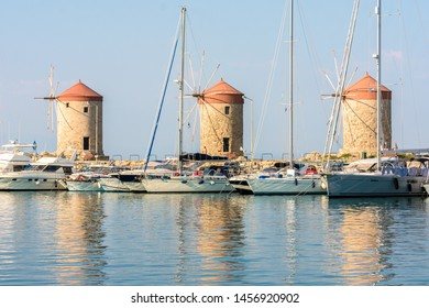 Rhodes, Greece - June 02, 2018. Rhodes, Greece - June 02, 2018. Sailing boats and Rhodes windmills in the background in Mandraki Harbour in Rhodes City