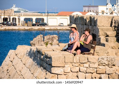 Rhodes, Greece - June 02, 2018. A couple female tourist sitting on the bench next to the Naillac Tower in an Old Harbour in Rhodes city on sunny day