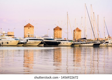 Rhodes, Greece - June 02, 2018. Luxury boats and Rhodes windmills in the background in Mandraki Harbour in Rhodes City