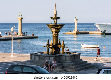 Rhodes, Greece - June 02, 2018. Fontana Grande on the Promenade in Mandraki Harbour in Rhodes City and people sitting on the steps on sunny afternoon