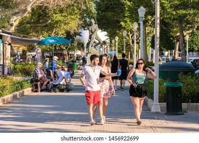 Rhodes, Greece - June 02, 2018. Walking young people on promenade in Mandraki Harbour on sunny afternoon