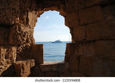 RHODES, GREECE - JUNE 12, 2018: Looking out to sea through the medieval fortified wall at Rhodes Old Town on the Greek island of Rhodes. The town is a UNESCO World Heritage Site.
