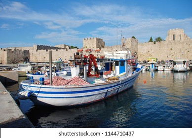 RHODES, GREECE - JUNE 12, 2018: Boats moored in Kolona harbour in Rhodes Old Town on the Greek island of Rhodes. The Old Town is a UNESCO World Heritage Site.