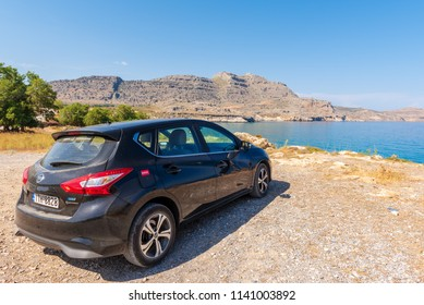 RHODES, GREECE - May 17, 2018: Nissan Pulsar car parked on the shore of Rhodes island with a beautiful view of the sea bay.