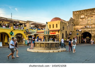 Rhodes, Greece - May 31, 2018. Hippocrates Square, people walking next to the Medieval fountain in The Medieval Old Town of the City of Rhodes