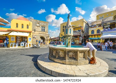 Rhodes, Greece - September 20 2018: A woman relaxes at the fountain in Old Town Hippocrates Square on a summer day on the Mediterranean island of Rhodes, Greece