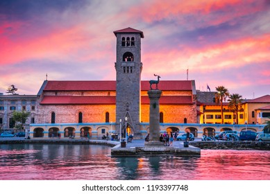 Rhodes, Greece. Stunning sunset image Mandraki harbour and Evaggelismos Church the place of Colossus of Rhodes.