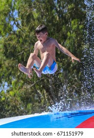 Rhodes, Greece-Jun 22,2017:Young boy  jumping on the wet bubble in the  water park  .Wet bubble is one of many popular game for adults and children in Water park.