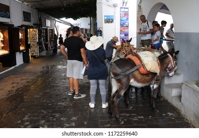 Rhodes Island. Lindos, Greece. 07/27/2018. Tourists in the historic town of Lindos, riding a donkey to go to the Acropolis on the hill.