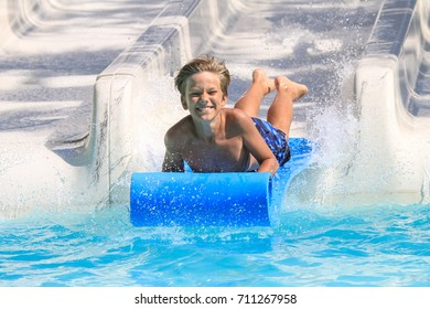 Rhodes,Greece-August  25,2017:The young boy on the mat racer slide in Water park.Mat racer slide is very popular for young people in the Water Park.
