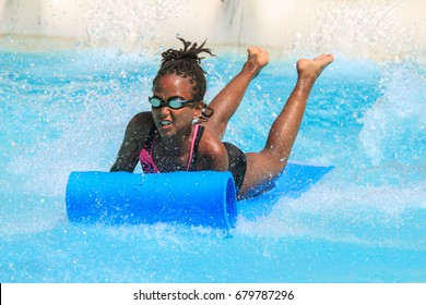 Rhodes,Greece-July 15,2017:Young happy girl gets into pool after landing on the mat racer slide.Mat racer slide is very popular for young people in the Water Park.