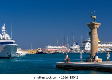 Rhodos, Greece - August 2016: Hirschkuh statue at the entrance from inner embankment in the Mandraki old harbour of the City of Rhodes, luxury cruise ships and yachts in background