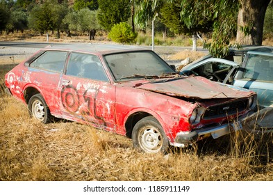 RHODOS, GREECE - SEPTEMBER 2015: Retro red abandoned car wreck