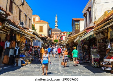RHODOS ISLAND, GREECE- JUNE 13: Many tourists visiting and shopping at market street in old town Rhodos, Greece on June 13, 2015. Shopping street leads to famous landmark of Suleymaniye Mosque.