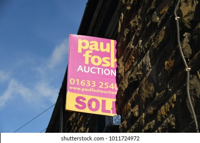 """Rhondda, Wales - January 2018: """"Sold at auction"""" sign fixed to the wall of a house"""