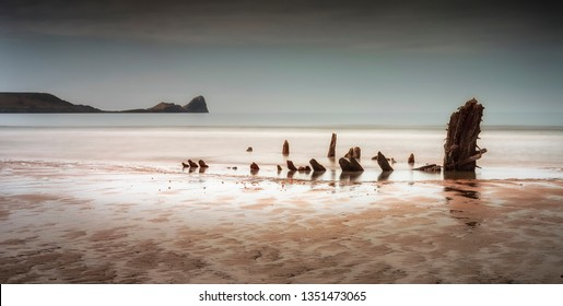 Rhossili Bay and Worms Head showing remains of the ship The Helvetia, a Norwegian barque, which was wrecked during a storm in 1887 on the Gower peninsula, South Wales UK