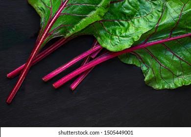 Rhubarb on dark background. Fresh red rhubarb stalks with green leaves, top view. Copyspace. Organic vegetarian food concept
