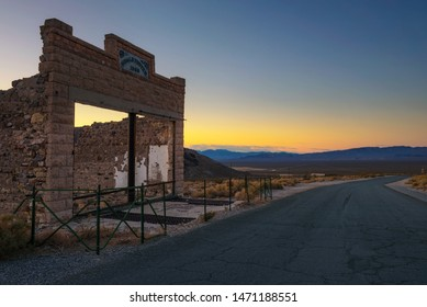 Rhyolite, Nevada, USA - October 23, 2018 : Sunset above abandoned building ruins in the town of Rhyolite, Nevada. This ghost town is located in Nye County among Bullfrog Hills near Death Valley.