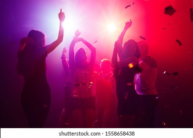 Rhythm. A crowd of people in silhouette raises their hands on dancefloor on neon light background. Night life, club, music, dance, motion, youth. Purple-pink colors and moving girls and boys.