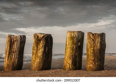rhythm golden beach smoke -Protective piles in the setting sun