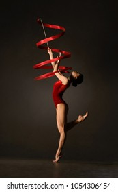 Rhythmic gymnast in red leotard with ribbon